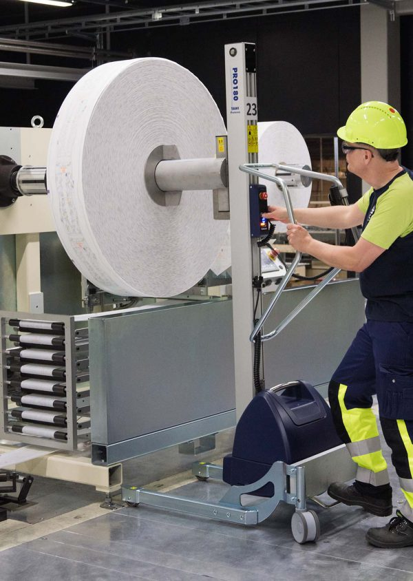 man loading roll onto machine axis with a lifting trolley