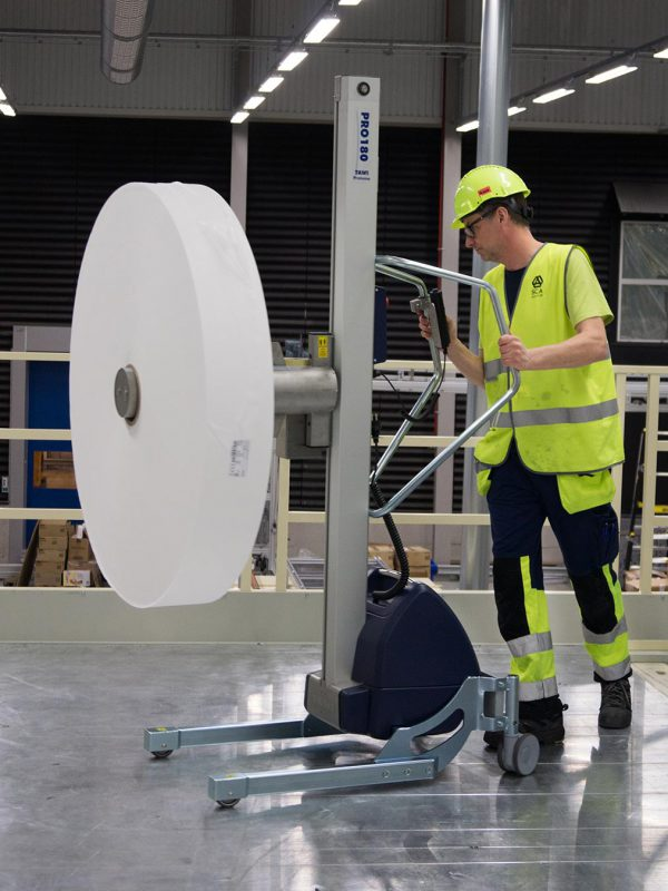man pushing lifting trolley loaded with large roll of paper