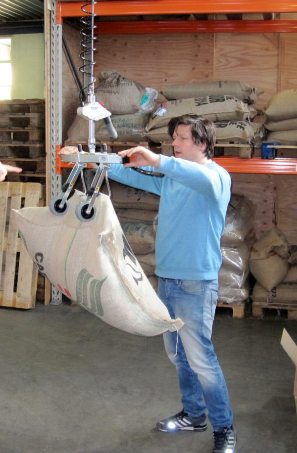 man lifting burlap sack with hoist lifter
