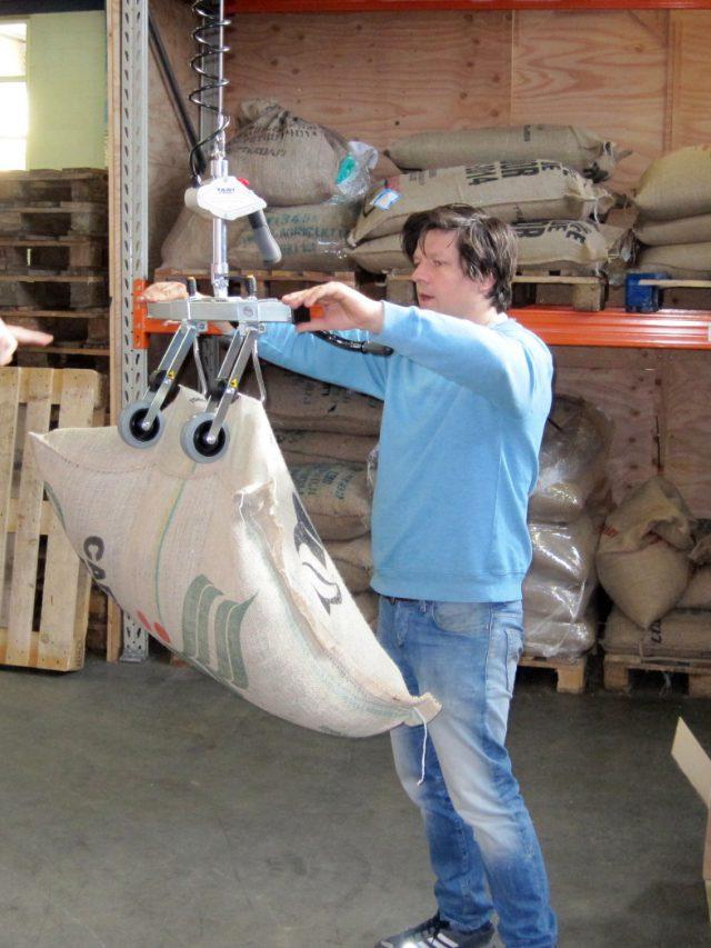 man lifting burlap sack with hoist lifter