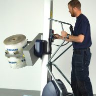 man lifting and turning roll in lifting trolley