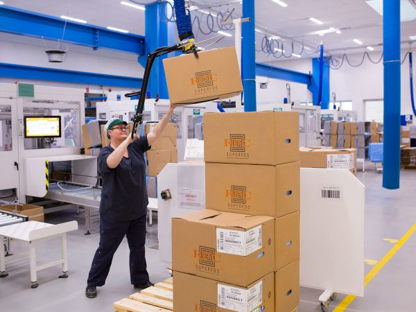 woman lifting box from high stack with handheld vacuum lifter