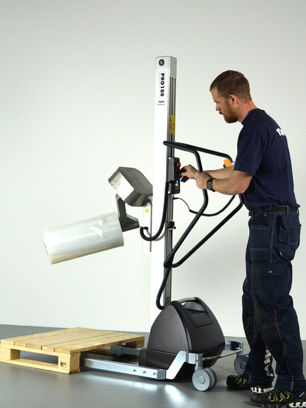 Man lifting and turning roll with coregripper tool on lifting trolley