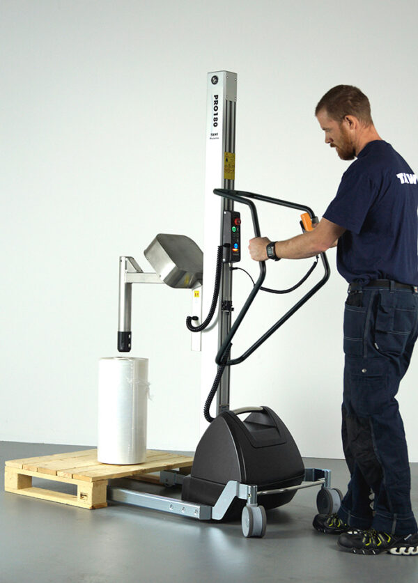 Man lifting roll with coregripper tool on lifting trolley