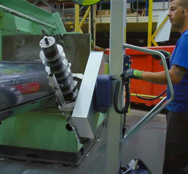 man using lifting trolley to load component into machine