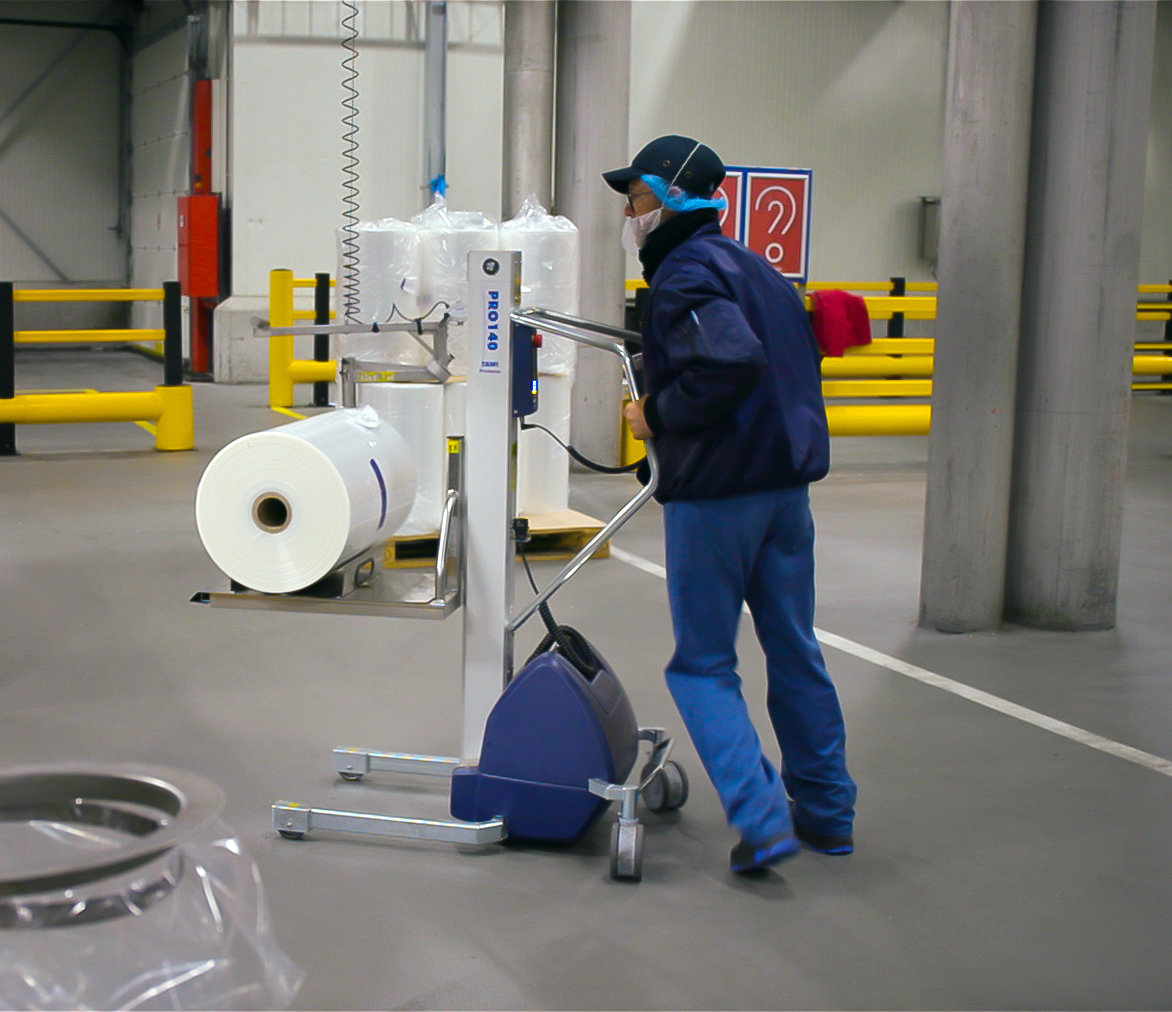 man pushing lifting trolley loaded with roll of plastic film