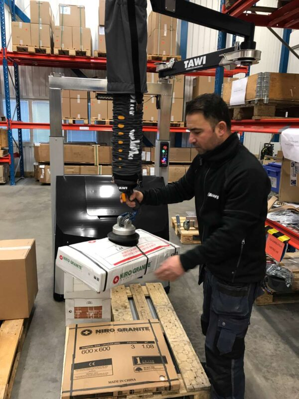 Man lifting box with handhold vacuum lifter in warehouse