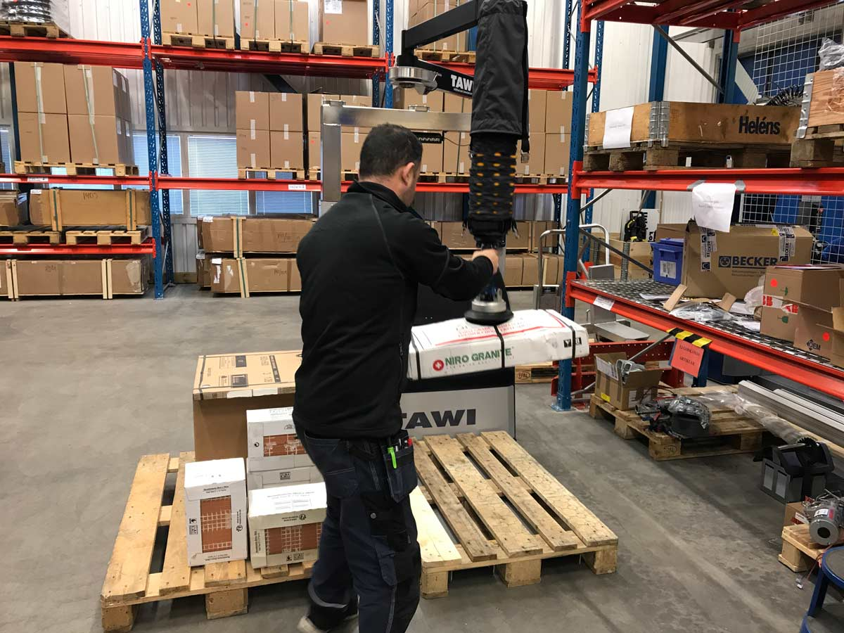 Man lifting box with handheld vacuum lifter in warehouse