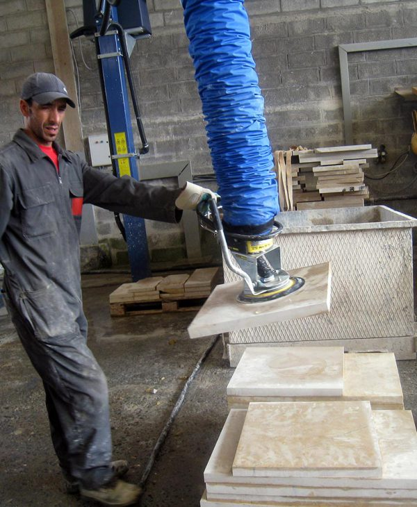 Man lifting stone slabs using handheld vacuum lifter