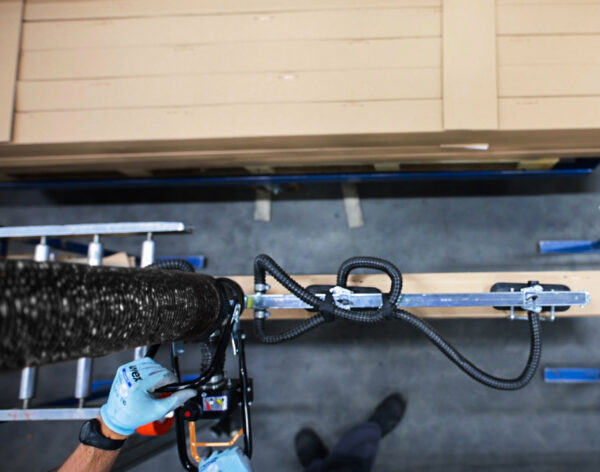 Hands using vacuum lifter gripping load of wood from above