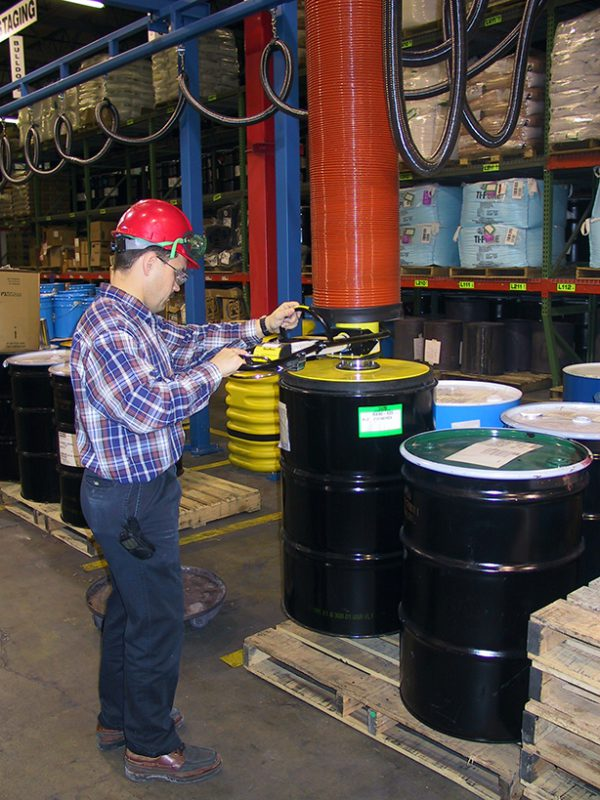 man lifting barrels from pallet using vacuum lifter