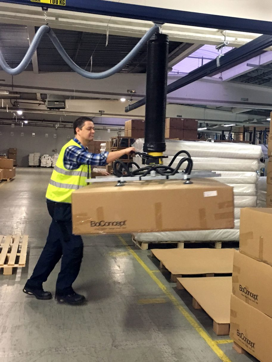 man lifting large box onto pallet with vacuum lifter
