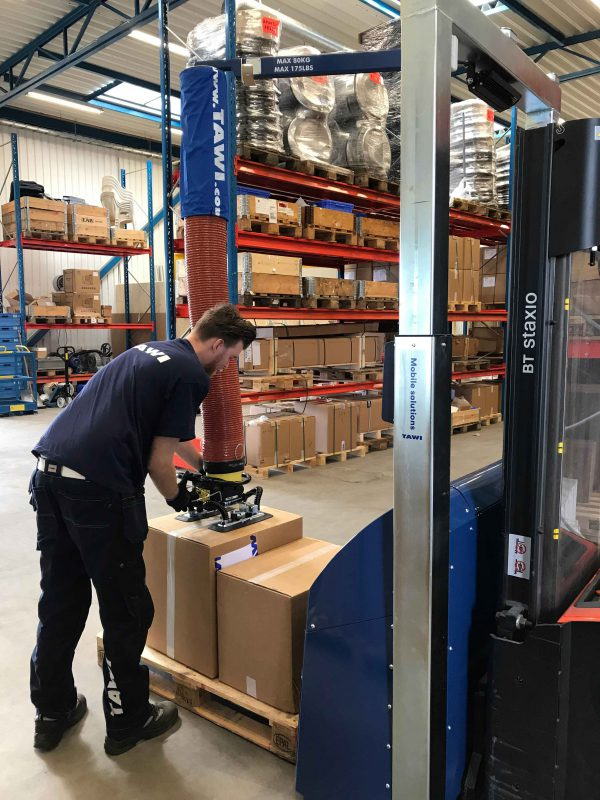 man lifting boxes in warehouse with mobile vacuum lifter