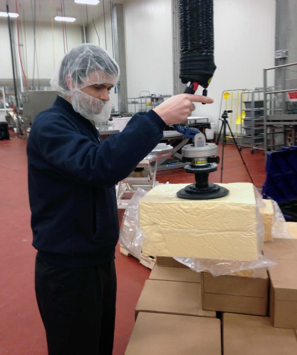 Lifting cheese block using handheld vacuum lifter