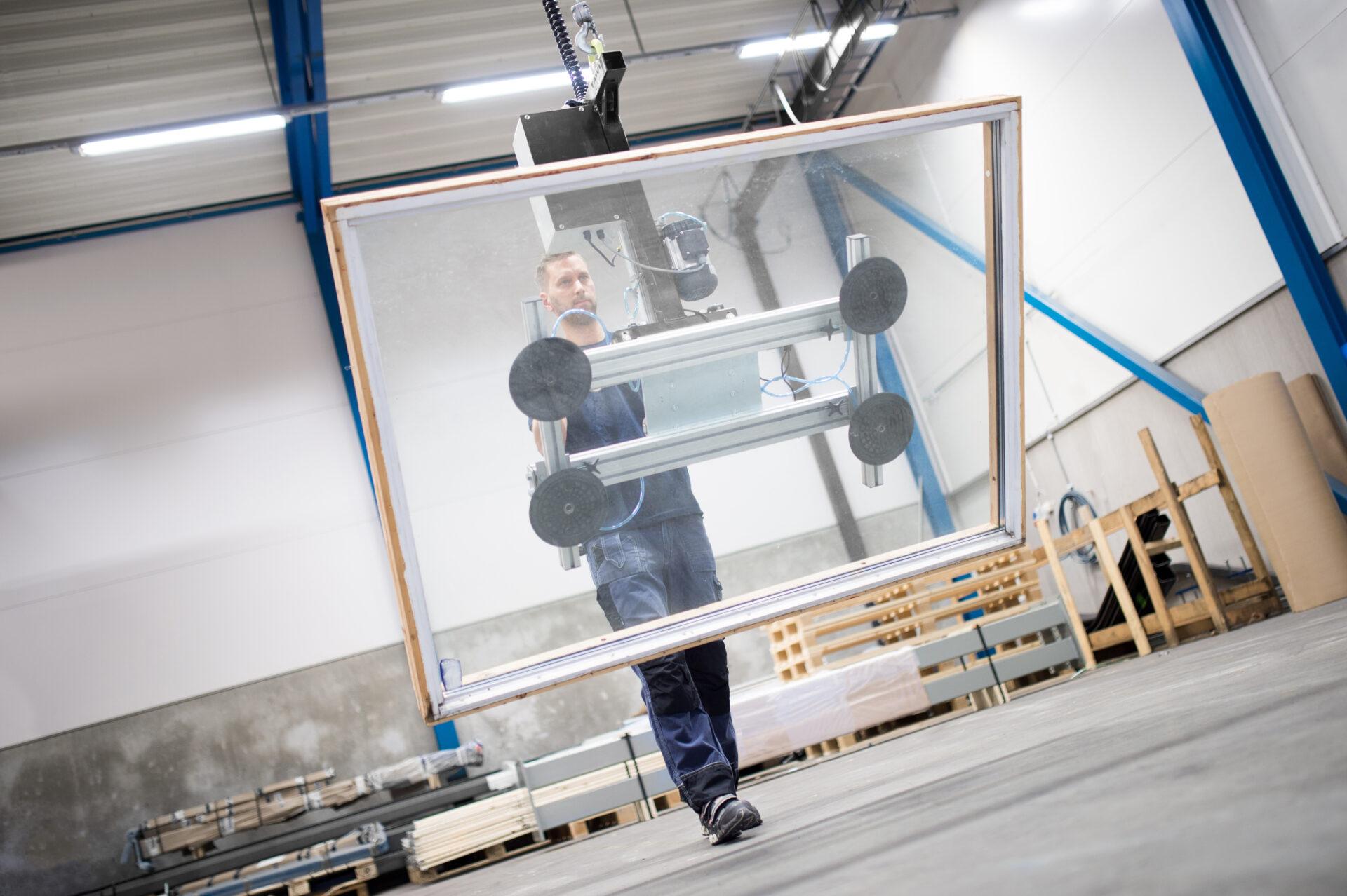 Man lifting window with vacuum yoke sheet gripper