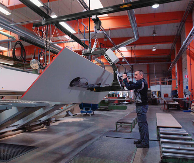 Man lifting large sheet of wood into CNC machine using vacuum gripper