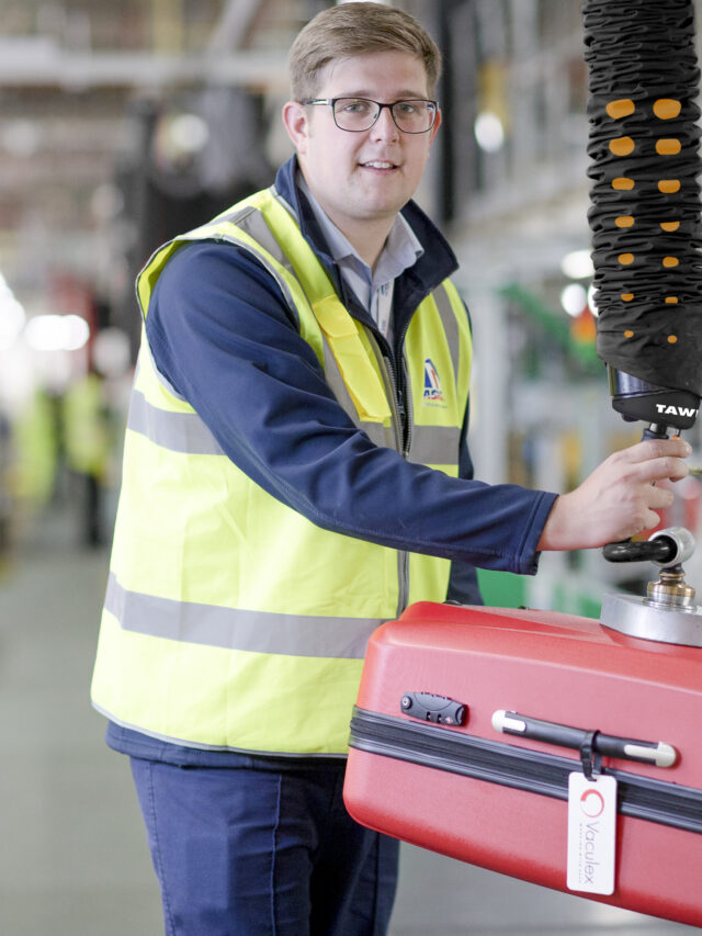 Man lifting heavy luggage with handheld vacuum lifter from airport luggage band in airport
