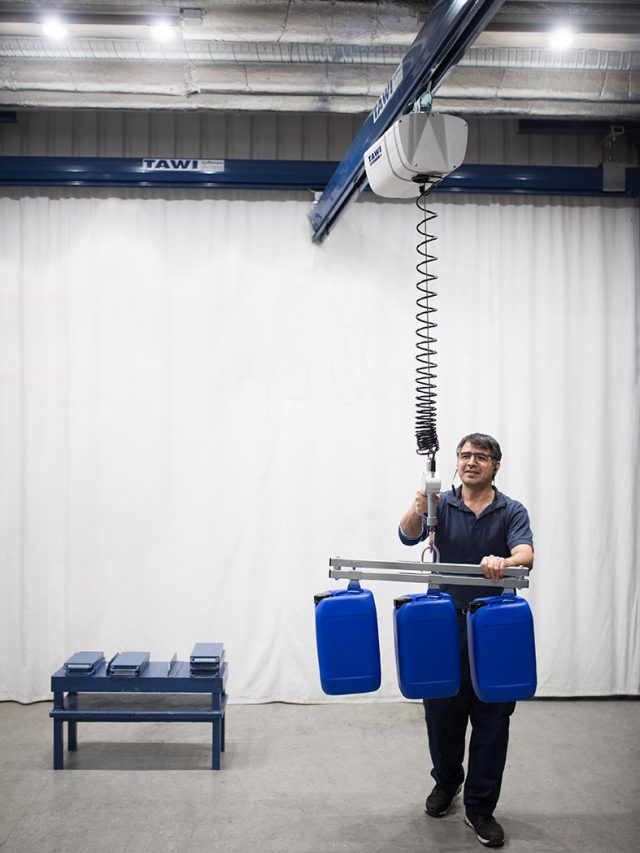 man lifting cannisters with wire hoist