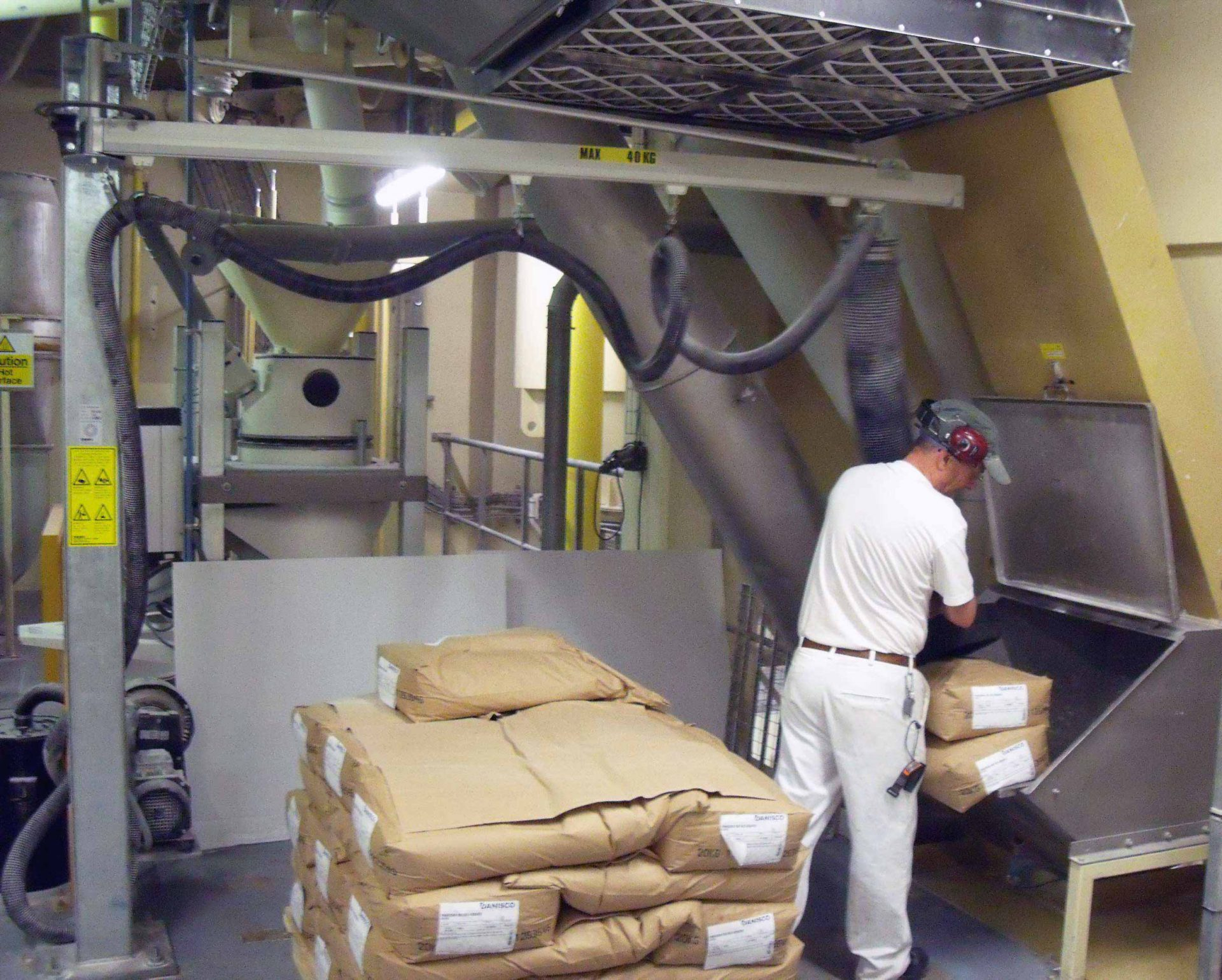 Man lifting paper sacks with vacuum lifter mounted in low built jib crane