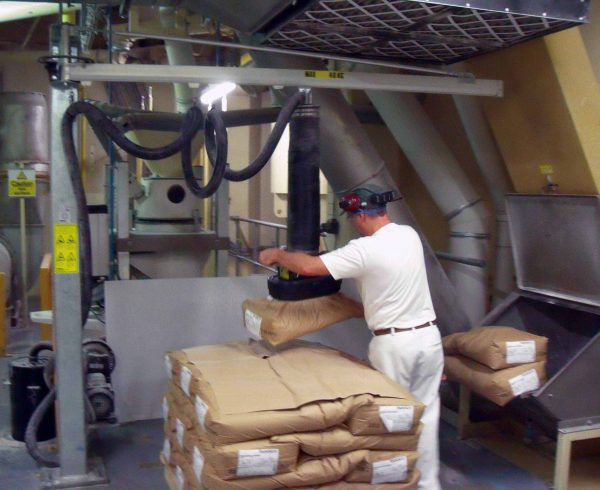 man lifting paper sacks using vacuum lifter mounted in low built jib crane