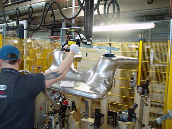 Man lifting automotive parts with handhold vacuum lifter