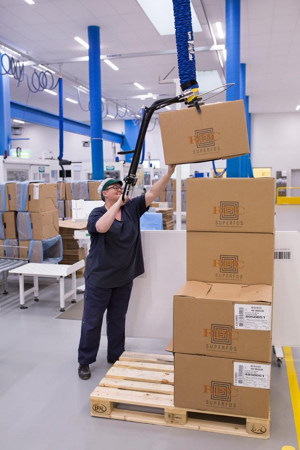Woman stacking boxes onto pallet using vacuum lifter