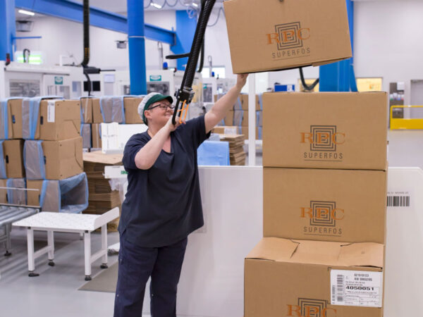 Woman lifting up and packaging boxes above her shoulder using a handhold vacuum lifter