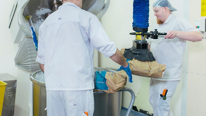 Lifting paper sacks and emptying contents into hopper