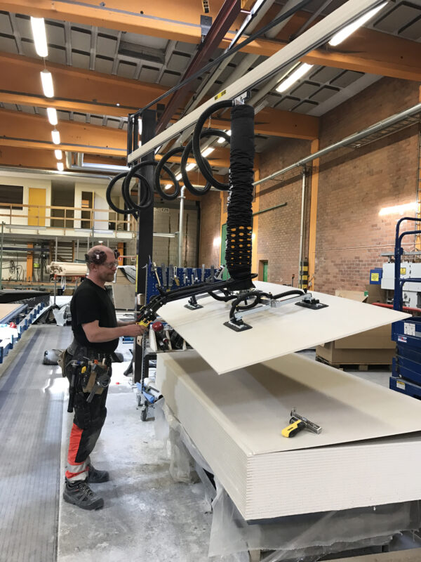 man lifting and tilting large sheet of wood using vacuum lifter system