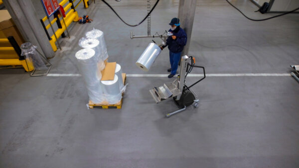 man transporting plastic roll with handhold lifting trolley in stock room