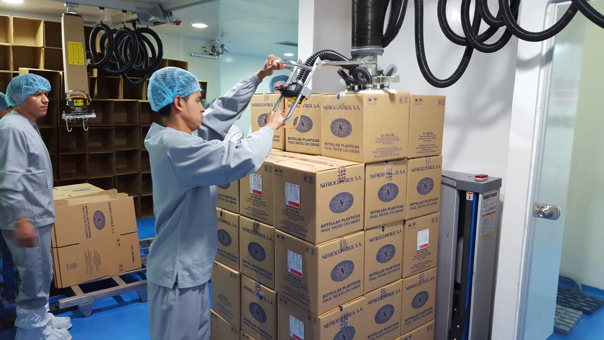 Woman tacking boxes on pallet using a handhold vacuum lifter