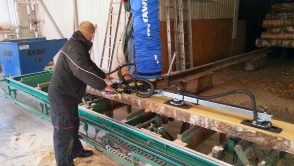 man lifting piece of wood using handheld vacuum lifter