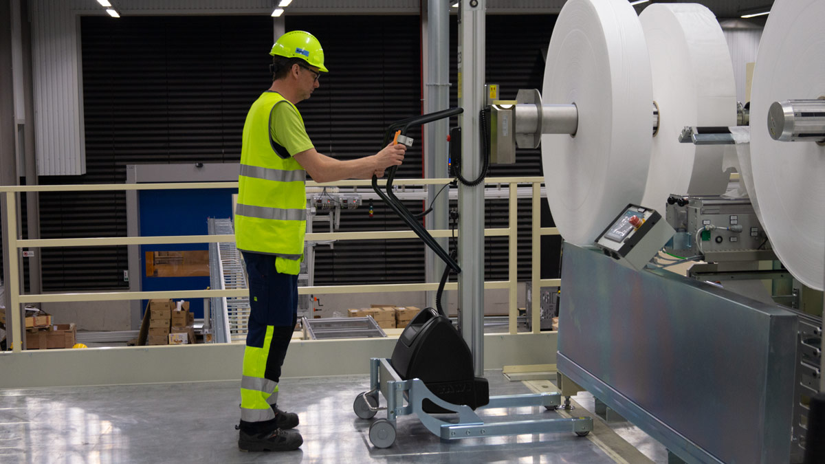 Man lifting and moving big plastic roll using a handhold vacuum lifter