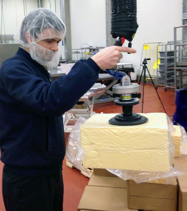 man lifting cheese using handheld vacuum lifter