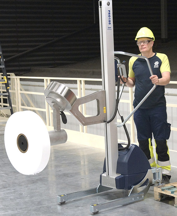 man pushing lifting trolley carrying roll of paper