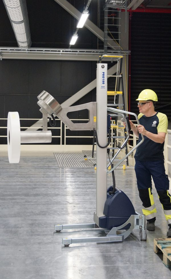 man pushing lifting trolley loaded with roll of paper