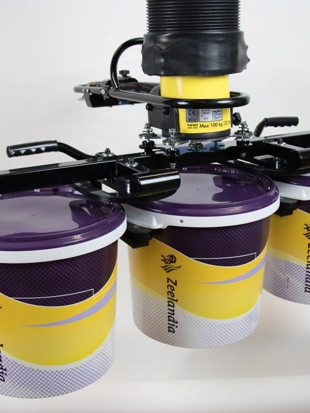 Vacuum lifter lifting three pails of paint