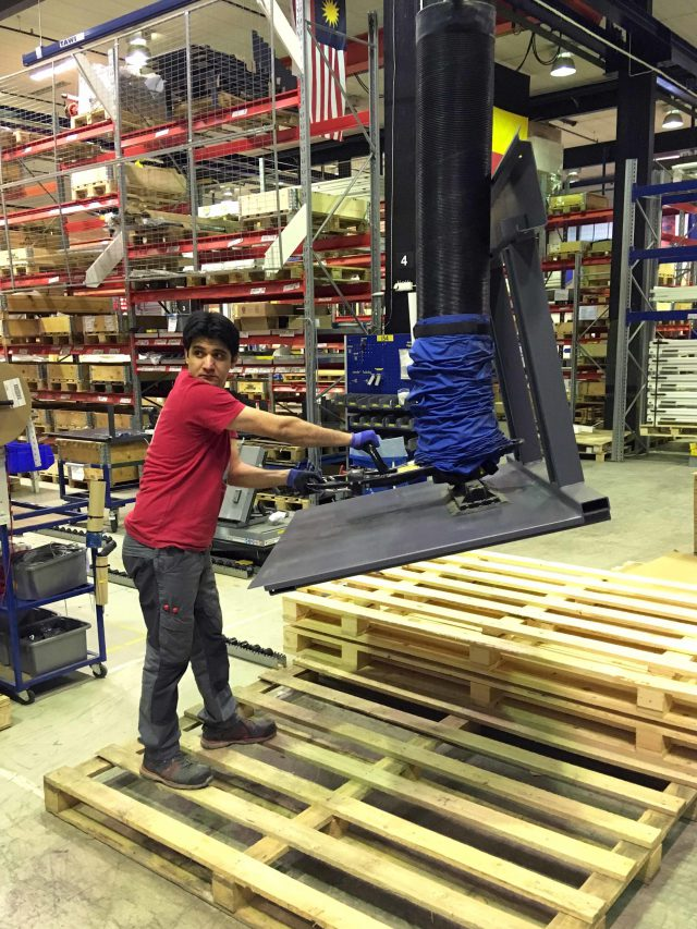 man lifting metal part using vacuum lifter