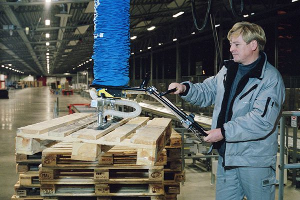 man lifting wooden pallet with vacuum lifter