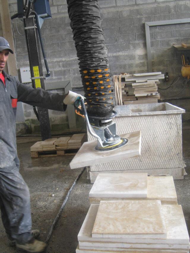 Man lifting stone block in Marocko using a handhold vacuum lifter