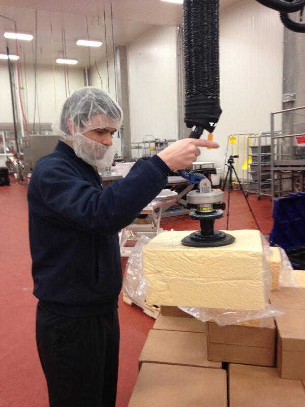 Man lifting cheese block using handheld vacuum lifter