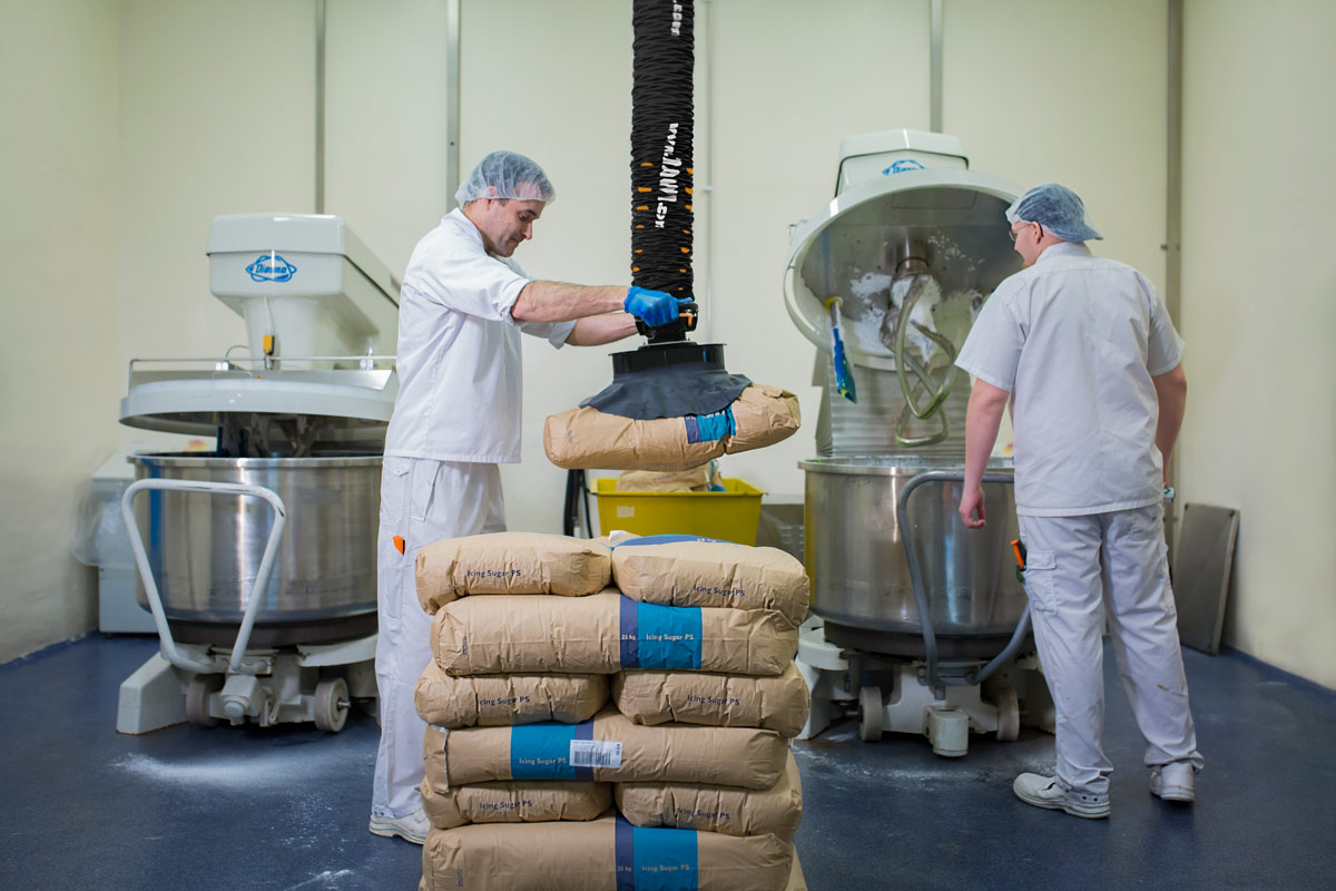 Two men lifting paper sack with food using handhold vacuum lifter
