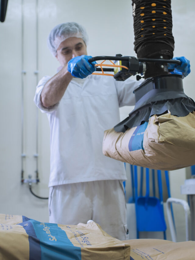 man lifting paper sack with handhold vacuum lifter