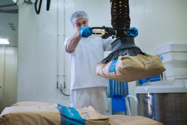 man lifting paper sack using handheld vacuum lifter in food industry