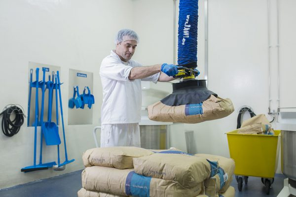 man lifting paper sack with vacuum lifter
