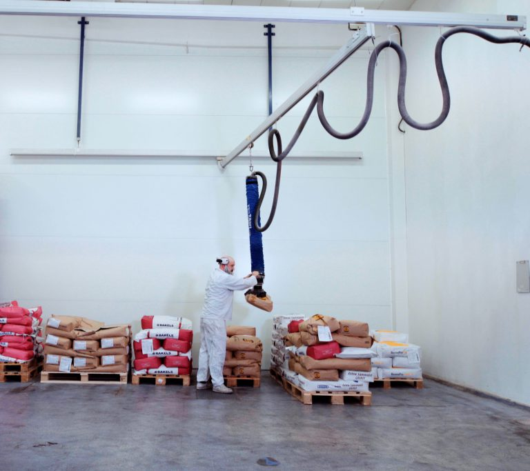 Person lifting bag of flour using a vacuum lifter suspended in overhead crane