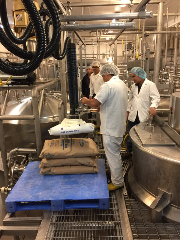 People in with clothes and hairnet lifting sacks using vacuum lifter in industry local