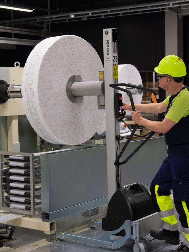Man lifting up big plastic roll using a handhold vacuum lifter