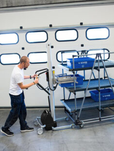 Man movig stacked trolley with boxes using a handhold vacuum lifter trolley
