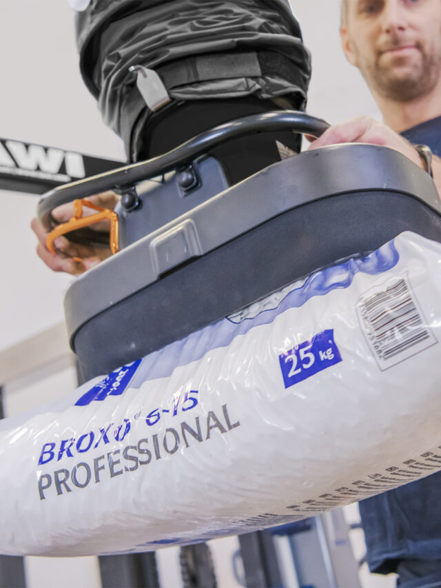 Man lifting up bag with help of a handhold vacuum lifter